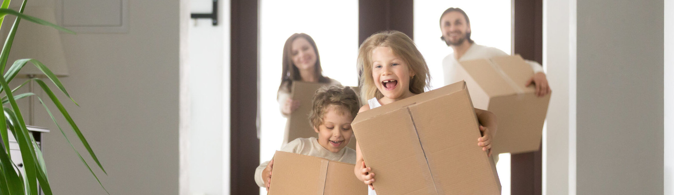 Couple and little kids with boxes running into new house